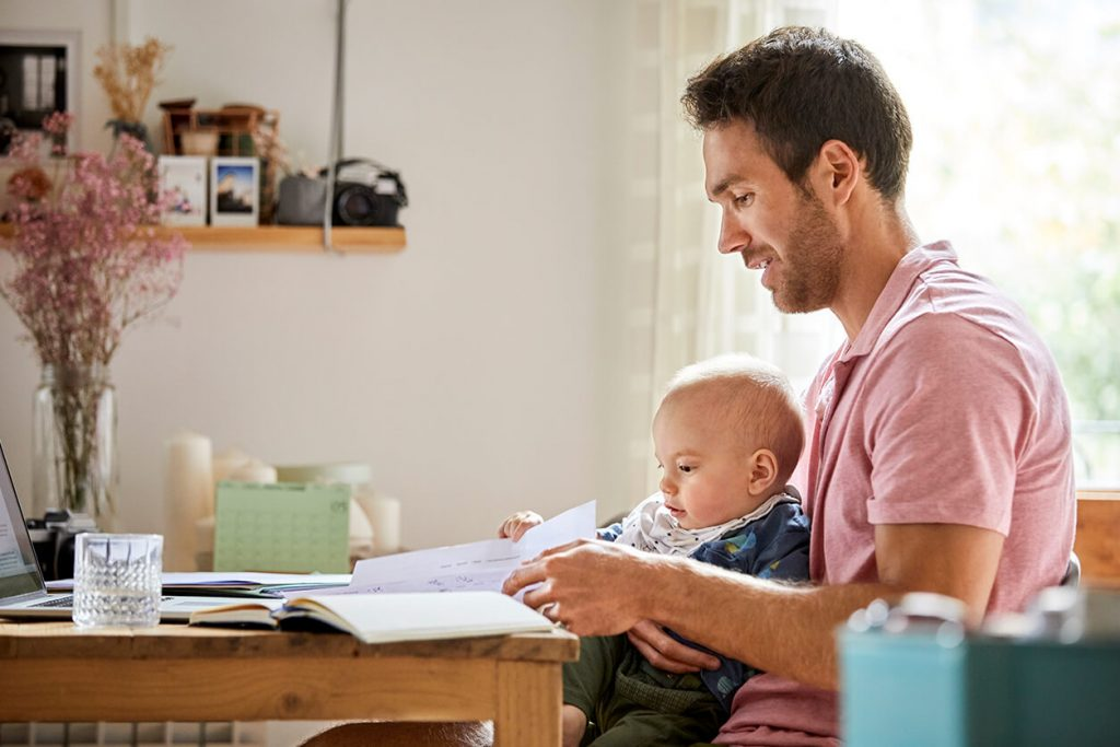 Man analyzing papers while holding son at table